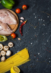 Pasta ingredients. Chicken breasts, Cherry tomatoes, spaghetti pasta and mushrooms on the dark stone table.