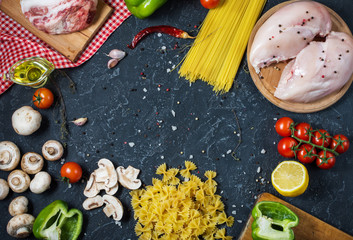 Pasta ingredients. Chicken breasts, Cherry tomatoes, spaghetti pasta, bacon and mushrooms on the stone table. Top view