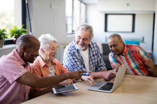Happy mixed race senior men and woman using laptop