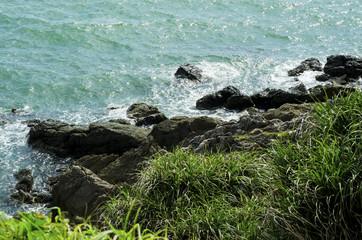 Green grass, rocks and a blue sea