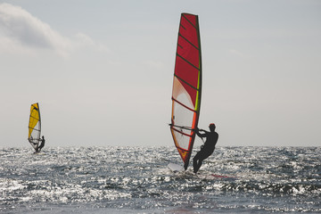 Back view of two windsurfers in action mooving parallel to each other