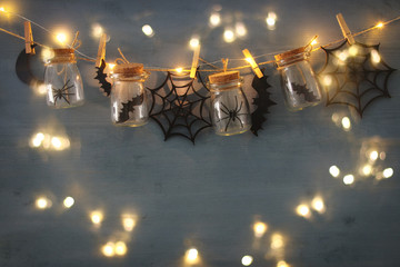 Halloween holiday concept. Masson jars with spiders, baths and wooden decorations