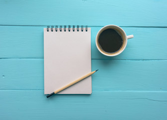 Notebook with a spring and Cup of coffee, a pencil. Bright blue, turquoise surface. Painted Board. Close-up, copy space. Top view
