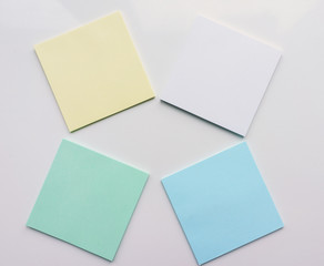 Four square sheet of paper on a white background. Top view. Close-up