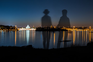 Couple standing holding hands looking at the scenery at night at Suomenlinna island in Helsinki Finland