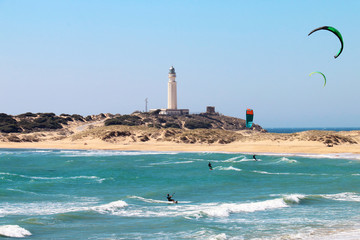 People doing kitesurfing on the beach of Los Canos de Meca, next to the lighthouse of Trafalgar, on the coasts of Cadiz, Spain