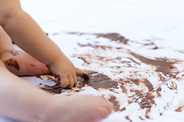 baby painting with hands with chocolate