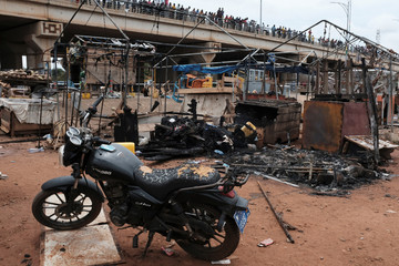 People stand on a bridge as they inspect the damage at the site of an explosion at a fuel distribution site in Accra