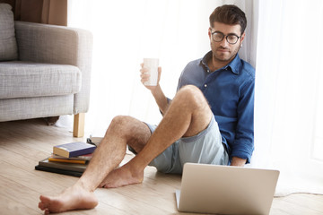 Hard working male scientific worker prepares report on laptop computer. Handsome student wears glasses, looks attentively at modern device, checkes e mails uses free internet connection at home