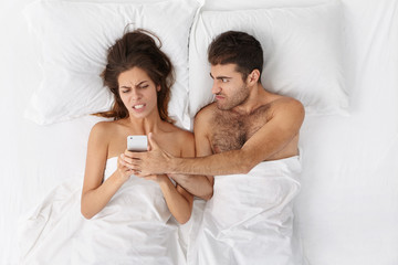 Young Caucasian couple fighting in bed: unshaven man trying to snatch mobile phone from his wife's hands who is spending night surfing internet isntead of paying attention to him and sleeping