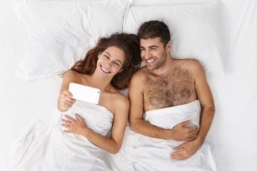 Top view of happy young European couple lying in bed on white linen and taking selfie on mobile phone, smiling broadly, enjoying calm and peaceful morning in hotel room on first day of honeymoon