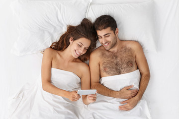 Cheerful young man and woman relaxing in bed before sleep and looking at mobile phone screen, making video conference call, talking to their friends online. People, relationships and technology