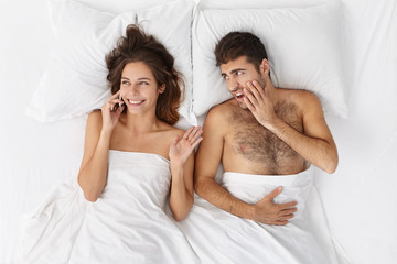 Top view of handsome bearded annoyed male staring amgrily at his wife who is lying next to him and talking nonstop using mobile phone and not letting her man sleep well. People and relationships