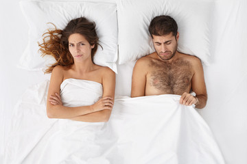 Attractive man feeling disappointed and depressed because of erectile dysfunction, looking at his penis under white cover, doesn't know what's the problem, angry wife lying next to him and waiting