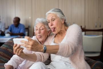 Senior women making face while taking selfie