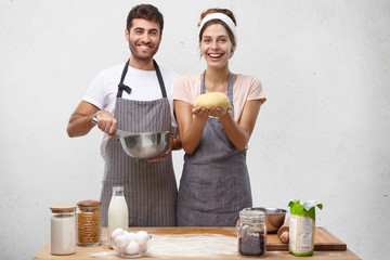 Products, food, cuisine and cooking concept. Portrait of happy positive young European couple baking homemade bread: bearded guy beating eggs in bowl while cute woman holding round shaped dough