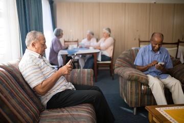 Senior men using mobile phone at nursing home