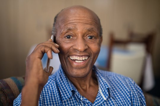 Portrait of cheerful senior man talking on mobile phone