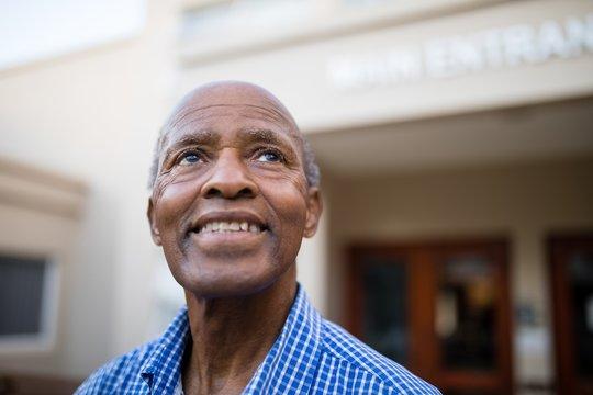 Thoughtful senior man smiling while looking up at nursing home