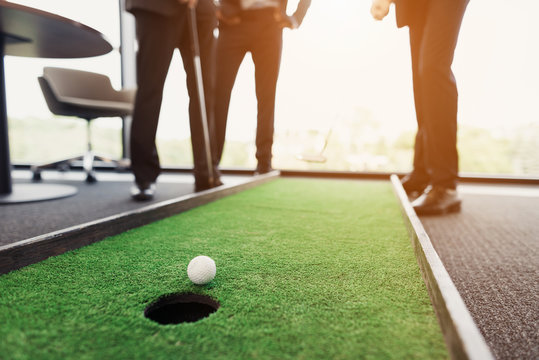 Close up. Men play in an office in a mini golf. One of them holds a golf club in his hands