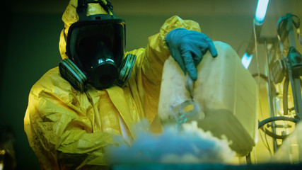 In the Underground Drug Laboratory Clandestine Chemist Wearing Protective Mask and Coverall Mixes Chemicals. He Pours Liquid From Canister into Bowl, Toxic Compounds Create Smoke.