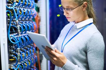 Portrait of female network engineer wearing glasses using digital tablet standing against server cabinets in data center