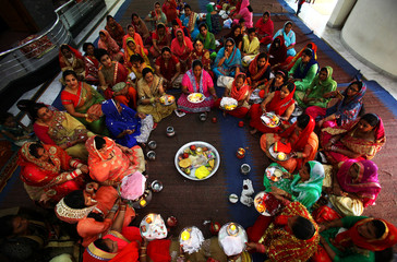 Married women pray for the well-being of their husbands during the Hindu festival of Karva Chauth, inside a temple in Chandigarh