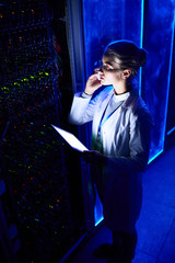 High angle portrait of beautiful female scientist working with supercomputer in futuristic neon light, speaking by phone and holding digital tablet