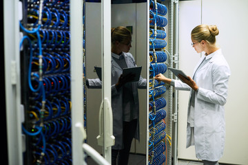 Portrait of young woman wearing lab coat working with servers in supercomputer research center, copy space