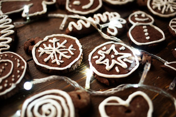 Traditional homemade Christmas ginger and chocolate cookies decorated with white sugar painting