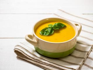 Homemade autumn pumpkin soup with basil leaf