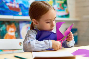 Portrait of cute little girl carefully cutting out heart shapes while making handmade card during art and craft class in pre-school