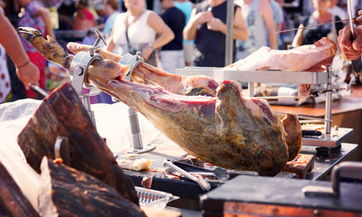 The seller in the market in Spain sharpens the knife for cutting the jamon, the national dish in the country