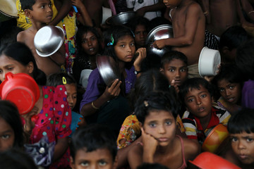 Rohingya refugee children wait for lunch at a refugee camp in Cox's Bazar