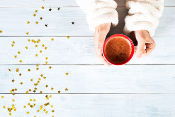 female hand holding cup of hot cocoa or chocolate on wooden table from above