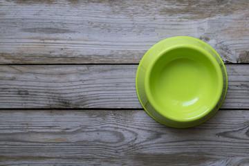Empty dog food bowl on wood table background