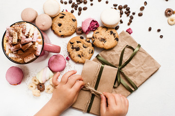 Christmas gifts and surprises from children. Little child preparing small presents for parents with cocoa and colorful macaroons, zephyrs and chocolate scones nearby. Top view picture