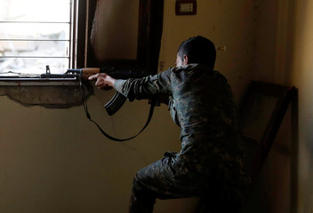 A bullet casing flies near the head of a fighter of Syrian Democratic Forces as he fires his weapon towards the Islamic State militants, at the frontline in Raqqa