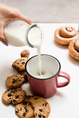 Pastry organic breakfast with milk and scones, close up. Woman pouring fresh lacto drink into cup near wholegrain cookies and baked rolls laying on white table