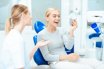 A woman is sitting at a dentist's reception. She looks in the mirror at her teeth. Woman smiling