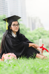 Happy graduate young Asian woman in cap and gown holding certificated in hand, Education concept