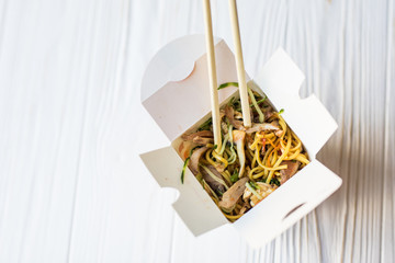 Chinese noodles in takeaway box on wooden background. Food.