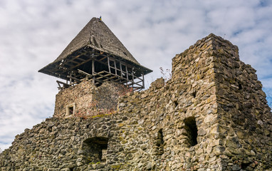 Nevytsky Castle, Ukraine - October 27, 2016: tower with wooden roof and stone wall of mighty Nevytsky Castle. popular travel destination of Transcarpathia