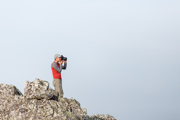 Nature photographer with digital camera on top of the rock