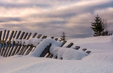 fallen wooden fence on snowy hillside. lovely rural scenery in winter