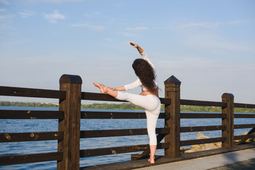 Young pregnant woman doing yoga outdoors. Pregnant yoga. Women doing different exercises. River on background. Concept of healthy lifestyle and relaxation, meditation.