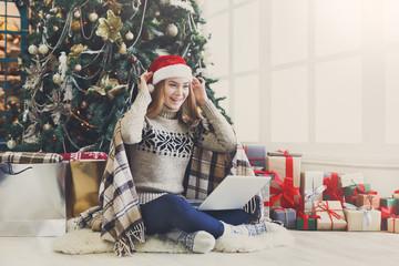 Happy girl in santa hat chatting online on laptop