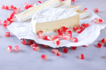 Camembert cheese, sliced cheese, lots of cheese with pomegranate seeds on white background
