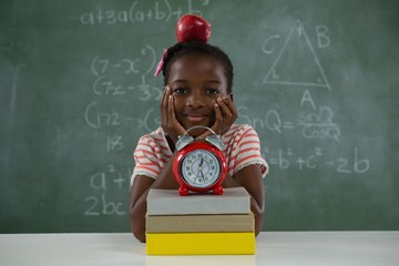 Schoolgirl sitting with red apple on her head against chalkboard