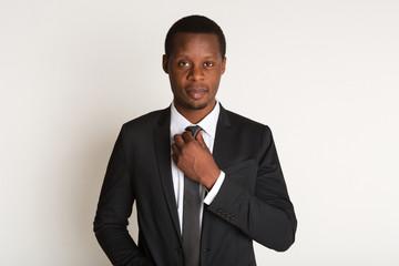 Black man manager straightens tie. Portrait